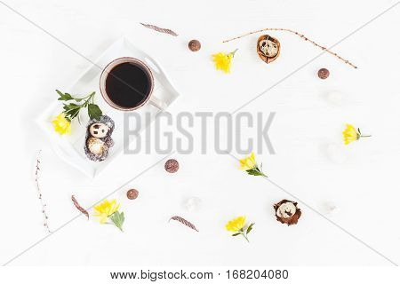 Workspace with cup of coffee easter eggs and yellow flowers. Easter concept. Flat lay top view