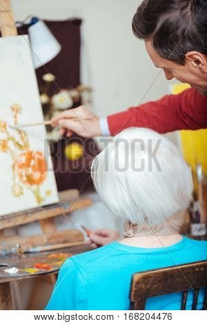 Be good. Professional young concentrated artist teaching elderly woman while drawing and spending time in painting school.
