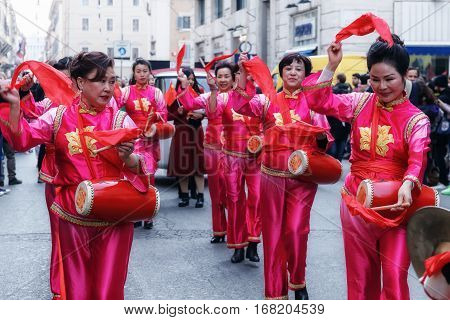 Rome Italy - January 28 2017: Chinese women in traditional dress play and dance through the streets of the capital during the procession celebrating the Chinese New Year in the year of the rooster.