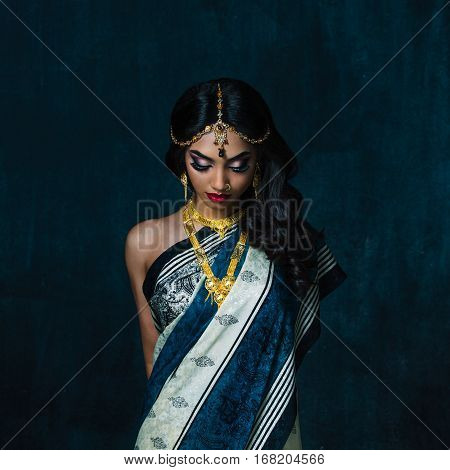 Bengali girl in a traditional costume with her eyes down in photostudio