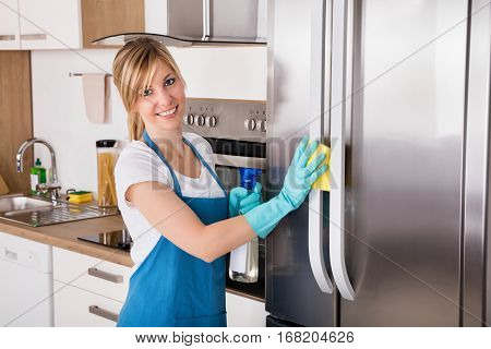 Young Smiling Professional Cleaning Service Woman Cleaning Refrigerator In Kitchen