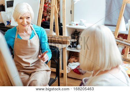 Common hobby. Elderly happy ambitious women talking and spending time in painting class while drawing.