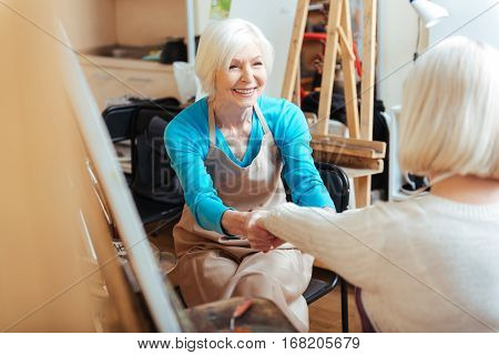 Creative cooperation. Elderly happy ambitious women talking and laughing in painting class while drawing.