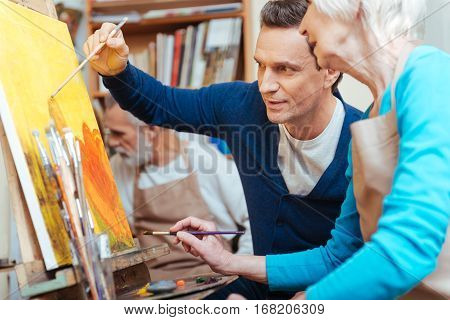 Good advisor. Delighted handsome young artist showing elderly woman how to paint while holding a brush and spending time in painting studio.