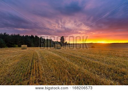 Beautiful Sunset Sky Over Stubble Field And Straw Bales