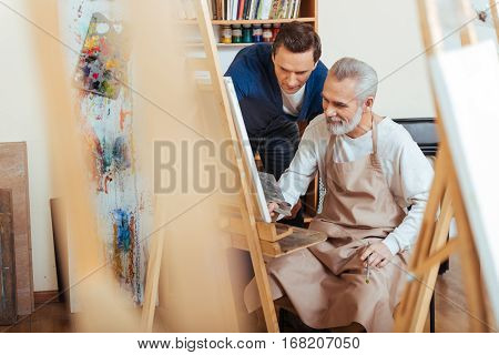 Good lesson. Glad handsome young artist helping elderly man while he painting and spending time in painting studio.
