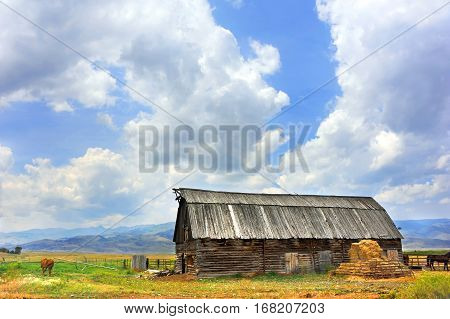 Rustic wooden log barn has beautiful mountain view in Happy Valley Montana. Barn has wooden roof.