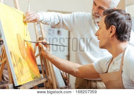 Paint it bright. Concentrated elderly professional artist painting while working with his young colleague and spending time in painting studio.