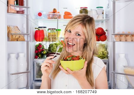 Young Happy Woman Eating Salad Near Opened Refrigerator