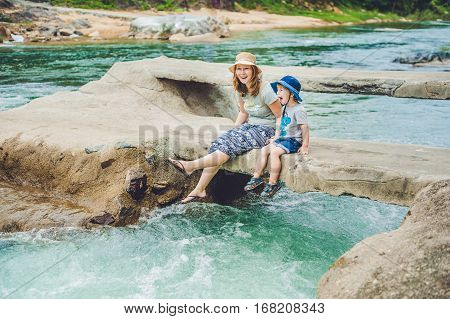 Mom And Young Son Sitting On Bridge On A Background Of The River