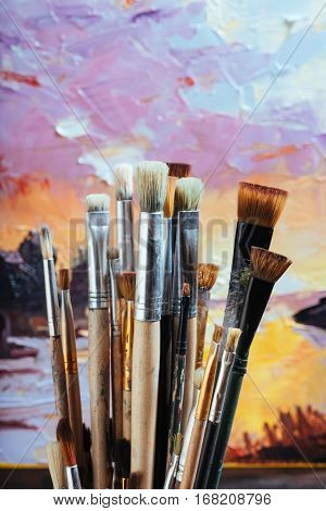 To be done. Close up of professional brushes and canvas colorful canvas with picture.