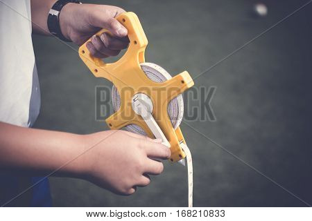 Boy Hand Holding Sport Measuring Tape Or Sport Equipment Tape Measure At Sport Field. Sport Equipmen