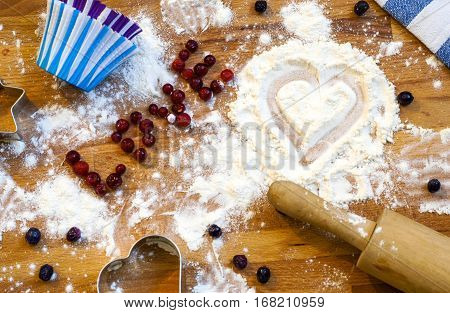 Heart of flour, rolling pin, berries and utensils for baking on wooden background.Happy Valentine's Day. Love and home