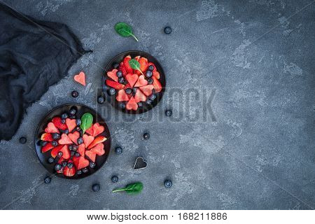 Fruit salad with watermelon strawberry blueberry on stone background. Valentine's day. Flat lay top view