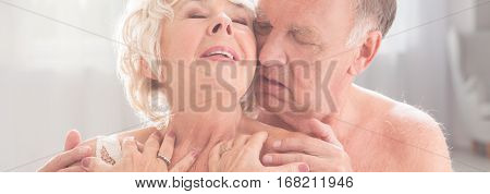 Senior Woman And Husband Embracing Her