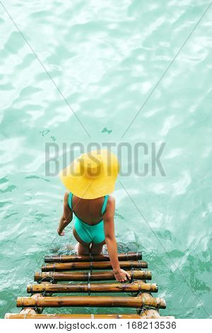 Woman in bikini and yellow hat entering sea water on bamboo stairs on the beach, top view.