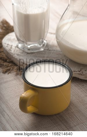 Glass pitcher yellow cup of kefir and napkin on a white table vertical
