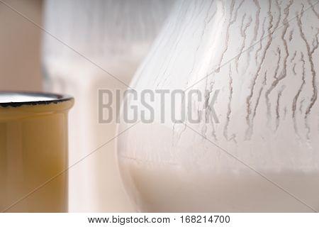 Glass pitcher yellow cup of kefir close-up horizontal