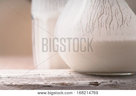 Glass and pitcher of white kefir on the old stand horizontal