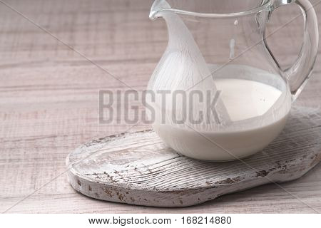Jug with kefir on a white stand on a wooden table horizontal