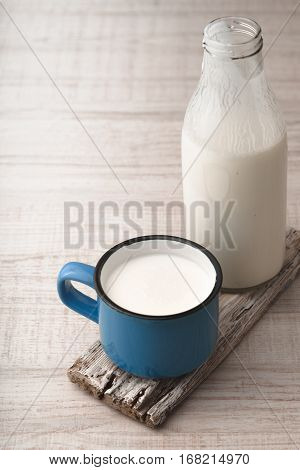 Blue cup with kefir and a bottle on a wooden stand vertical