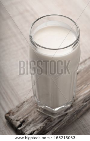 Glass kefir on a wooden stand on the table vertical