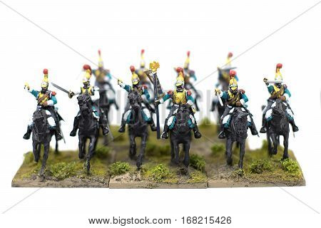 A large group of French Napoleonic toy soldiers on horseback charging toward the viewer against a white background