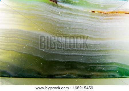 A beautiful close-up photo of a green Agate texture with inlays of different colors. All this creates a clean abstract background.