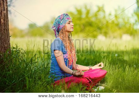 Young girl meditating in the park. Girl with pigtails in a turban meditating sitting on the grass on a sunny day