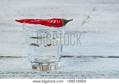 Shot of vodka with cayenne pepper on an old white wooden table
