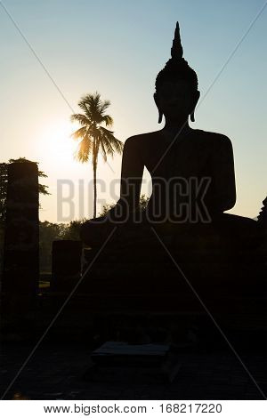 Ancient sculpture of a sitting Buddha in ruins of Wat Tra Phang Ngoen at sunset. Sukhothai, Thailand