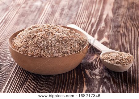 Wheat bran in wooden bowl on a wooden table