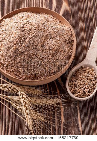 Wheat bran in wooden bowl and ears of wheat on a wooden table