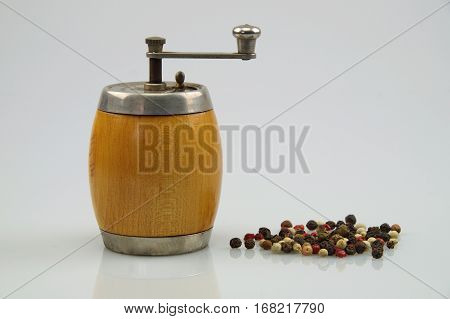 pepper with a old wooden mill on a white background