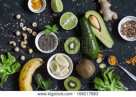 Green smoothie ingredients. Cooking healthy detox smoothies. On a dark background top view