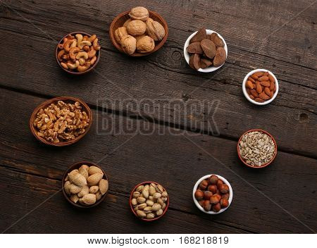 Group of delicious dried fruits over a wooden background. Nuts almonds pistachios