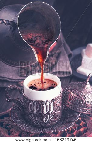 Turkish coffee pouring into traditional embossed metal cup. Toned