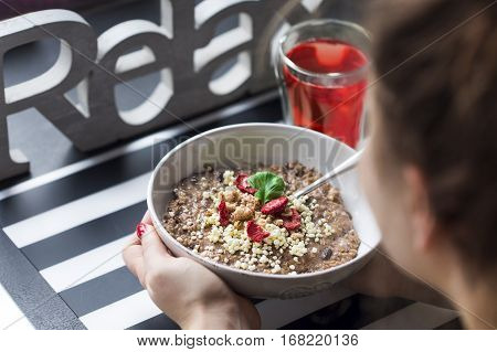 Breakfast with  chocolate oatmeal prepared by a woman, puffed rice, cereals , dried strawberries in white bowl and  green tea