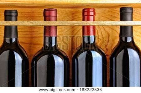 Four red wine bottles in a wooden case. Closeup filling the frame.