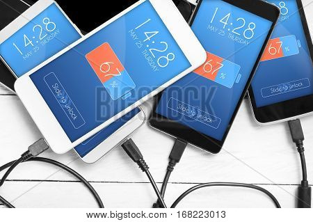 Stack Of Smartphones Connected To Power Source. Concept Of Low Battery Level  Problems