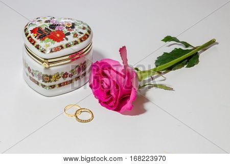 Romantic Valentines day content with decorated jewel case along with pink rose and gold engagement rings isolated in white background.