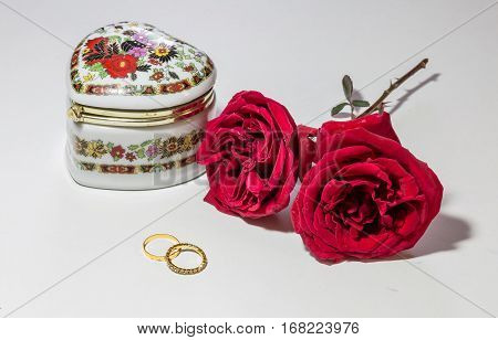 Romantic red roses with engagement rings and artistic jewelry case for Valentines Day isolated in white background.