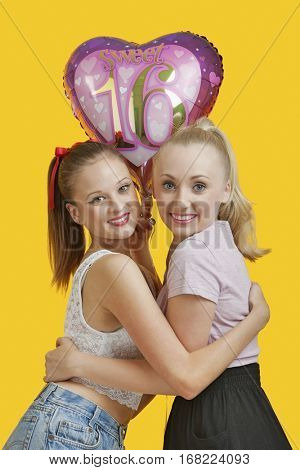 Portrait of two happy young women with birthday balloon hugging over yellow background