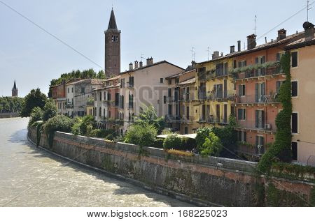 VERONA, ITALY - AUGUST 6, 2014: Buildings at the riverbanks of the Adige River in Verona Italy.