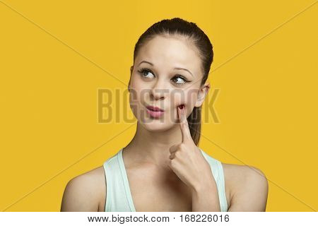 Thoughtful young woman looking sideways over yellow background