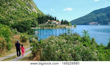 grandfather and grandchild walking on charming coastal of Kotor Bay in front of Banja Monastery, Montenegro