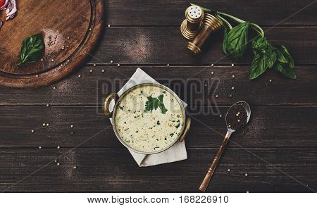 Vegan and vegetarian dish, cold summer yoghurt raita soup in copper bowl. Indian cuisine meal on wooden served table background. Healthy eastern local restaurant food above view
