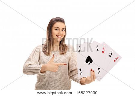 Joyful young woman holding four aces and pointing isolated on white background