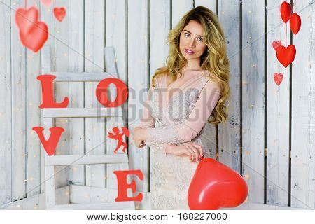 Beautiful Happy blonde girl with blue eyes portrait in a lace dress holding a red heart. Romantic scene. Red hearts and Love text. Red and White background