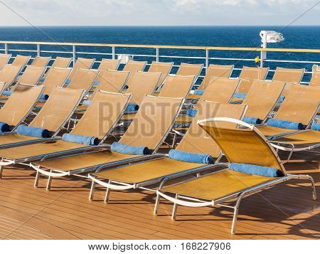 many empty chairs on outdoor deck on stern of cruise liner
